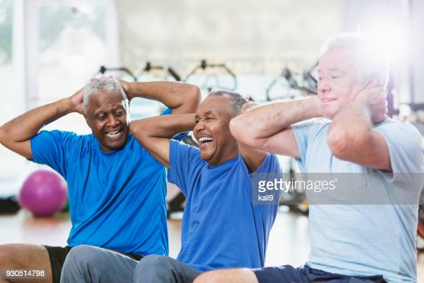 Three multi-ethnic senior men in gym exercising