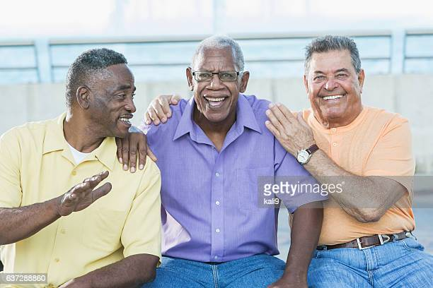 Three multi-ethnic senior men on bench outdoors