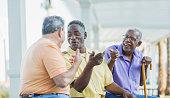 Three multi-ethnic senior men on bench talking