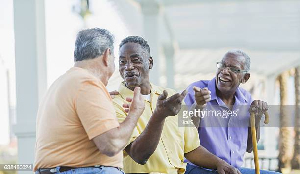 three multi-ethnic senior men on bench talking - walking cane stock photos and pictures