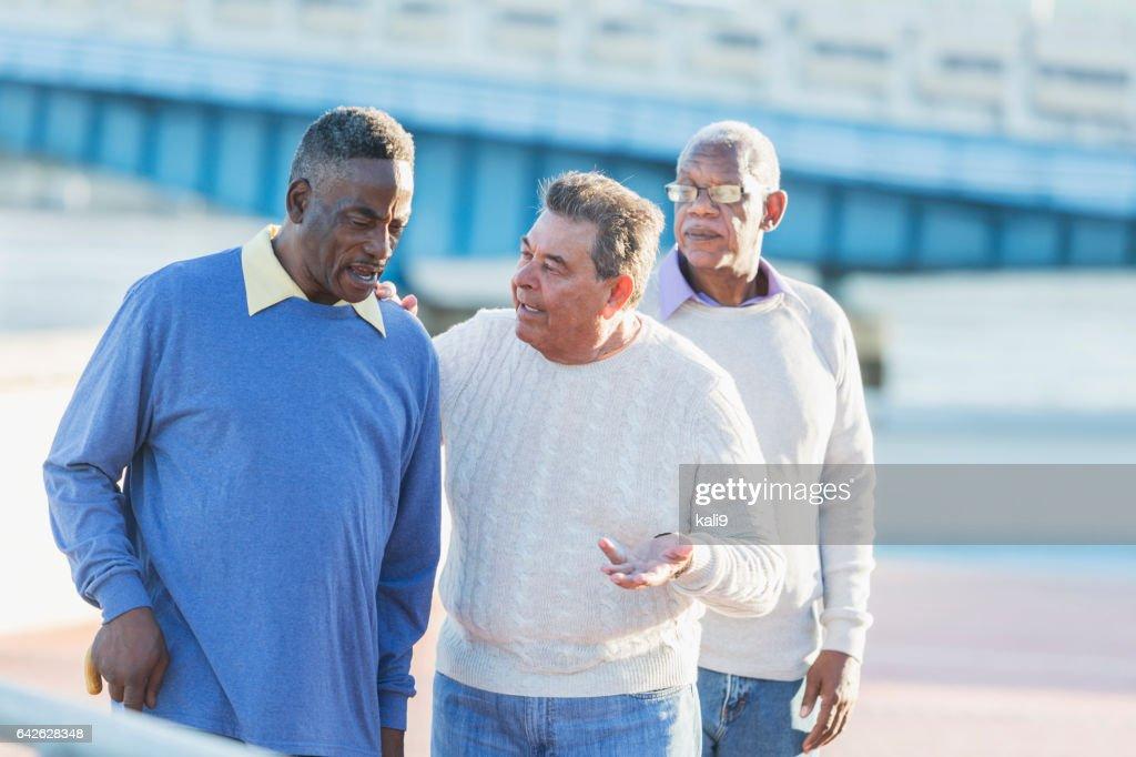 Three multi-ethnic senior men, serious conversation : Stock Photo