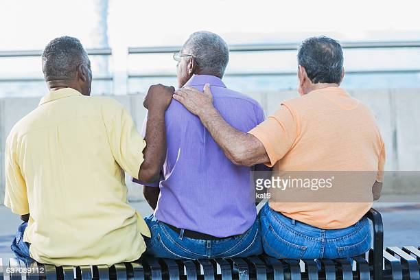 Three multi-ethnic senior men sitting on bench