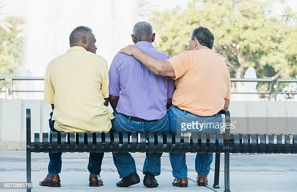 three multi-ethnic senior men sitting on bench - vieilles fesses photos et images de collection
