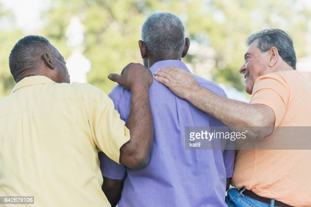 three multi-ethnic senior men sitting on bench - hand on shoulder stock pictures, royalty-free photos & images