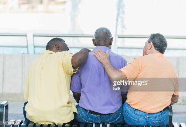 three multi-ethnic senior men sitting on bench - african american man helping elderly stock pictures, royalty-free photos & images