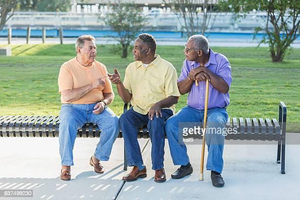 three multi-ethnic senior men sitting on bench talking - fotostock stock-fotos und bilder