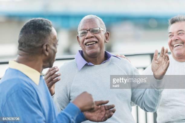Three multi-ethnic senior men talking and smiling