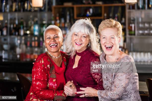 three multi-ethnic senior women at a bar - cocktail dress stock pictures, royalty-free photos & images