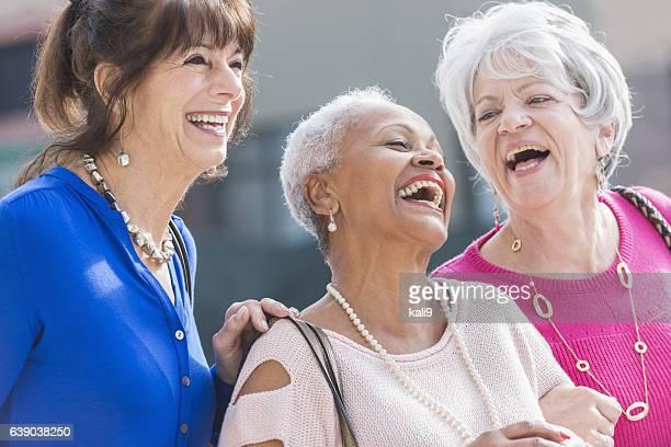Three multi-ethnic senior women laughing