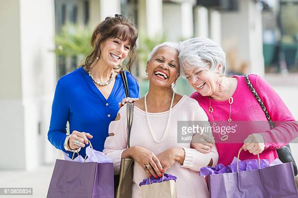 three multi-ethnic senior women out shopping - three people stock pictures, royalty-free photos & images