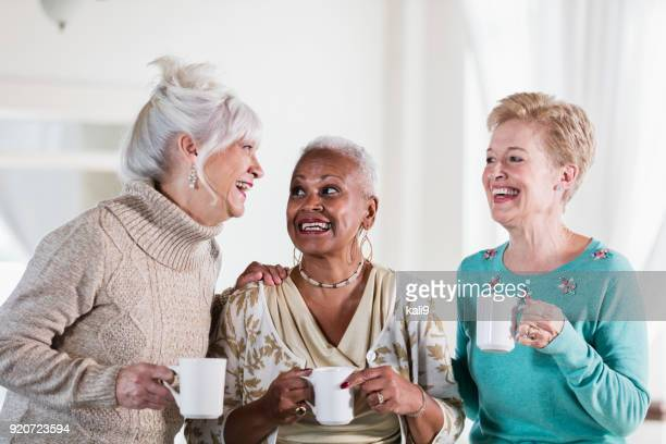 three multi-ethnic senior women socializing over coffee - brightly lit stock photos and pictures
