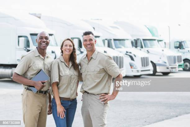 Three multi-ethnic workers in front of semi-trucks