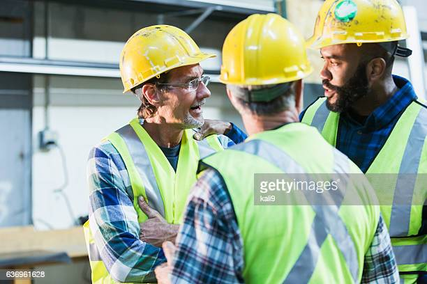 three multi-ethnic workers with safety vests and hard hats - hand on shoulder stock pictures, royalty-free photos & images