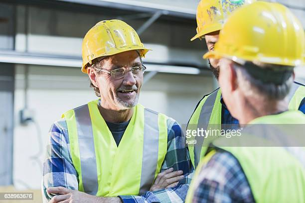 Three multi-ethnic workers with safety vests and hard hats