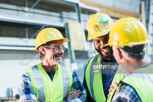 3 人の多民族労働者安全ベストとヘルメット