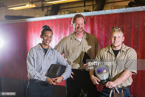 Three multi-ethnic workers with welding equipment