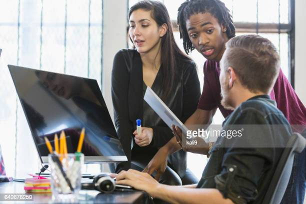 Three multi-ethnic young office workers around computer