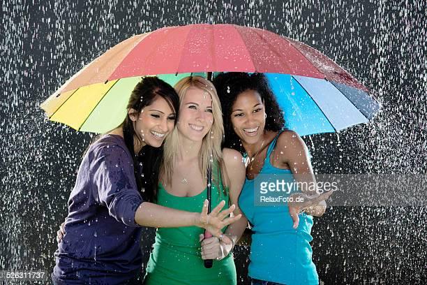 Tres multiétnico mujeres jóvenes con sombrilla mientras disfruta de lluvia