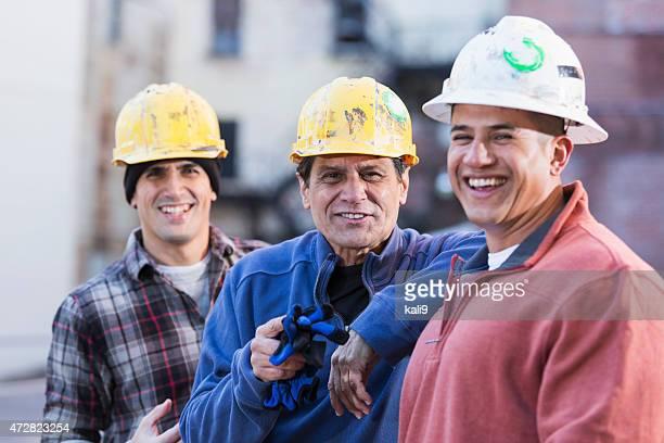 Tres multirracial trabajadores de la construcción usando cascos rígidos