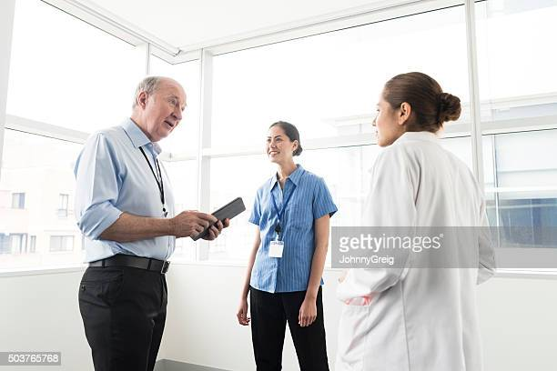 Three multiracial medical professionals discussing in hospital