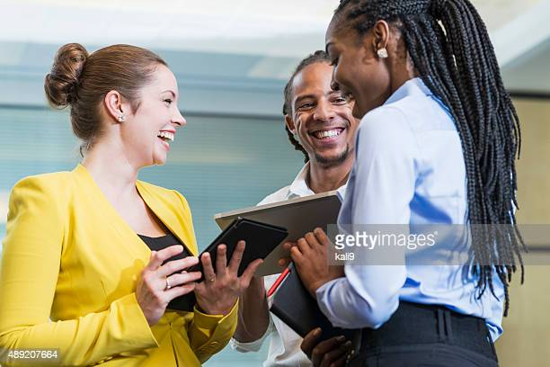 Three multi-racial office workers talking and laughing