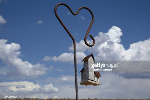 three multi-sized birdhouses hang from a heart shaped pole; blue sky and puffy clouds beyond - timothy hearsum stock-fotos und bilder