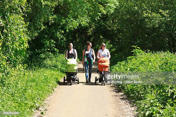 three mums walking with their babies - s0ulsurfing stock-fotos und bilder