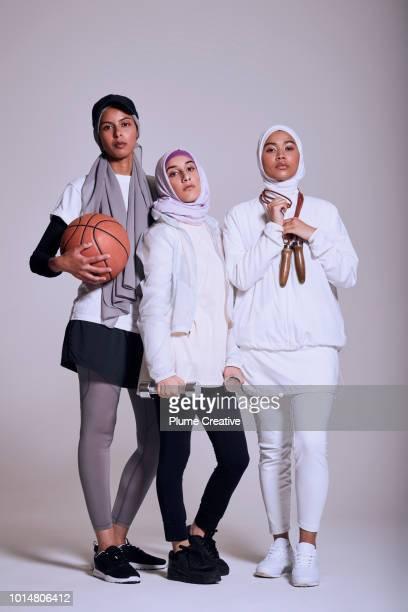 Three Muslim women in fitness wear looking at camera