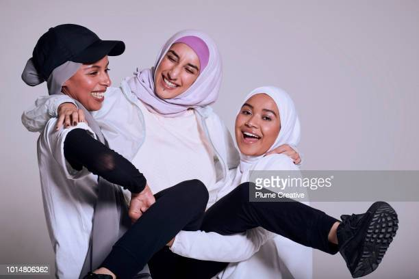 Three muslim women laughing togehter