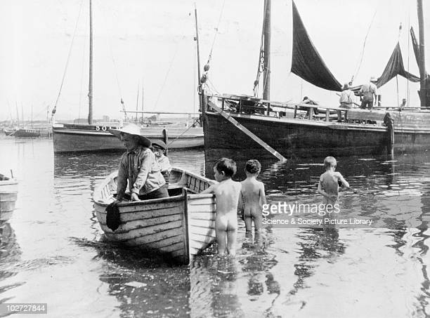 Three naked boys wading into the harbour England 1900s Three naked boys wading into the harbour whilst two other boys stay in their dinghy c 1900s...