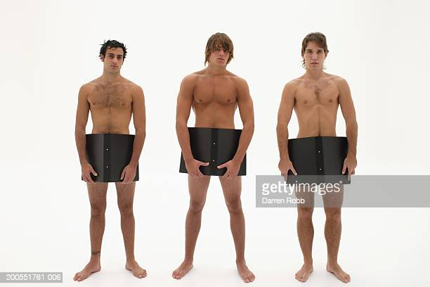 Three naked young men covering groin with black office folders, portrait