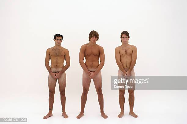 Three naked young men standing in line, hands covering groin
