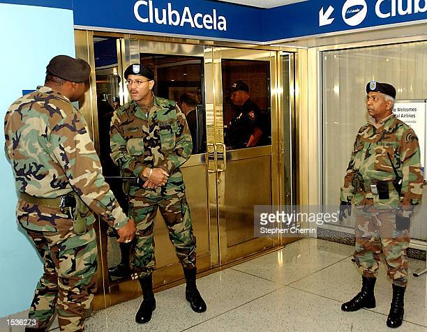 Three National Guardsman stand by the Amtrak Club Acela speaks during a media conference as two Amtrak policemen stand by October 28 2002 at Penn...