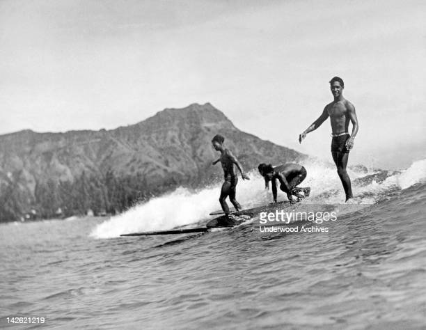 Three native surfers ride their boards with ease at Waikiki Beach with Diamond Head in the background Honolulu Hawaii 1920s