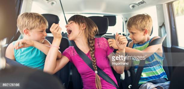 three naughty kids fighting in a car - family inside car stock photos and pictures