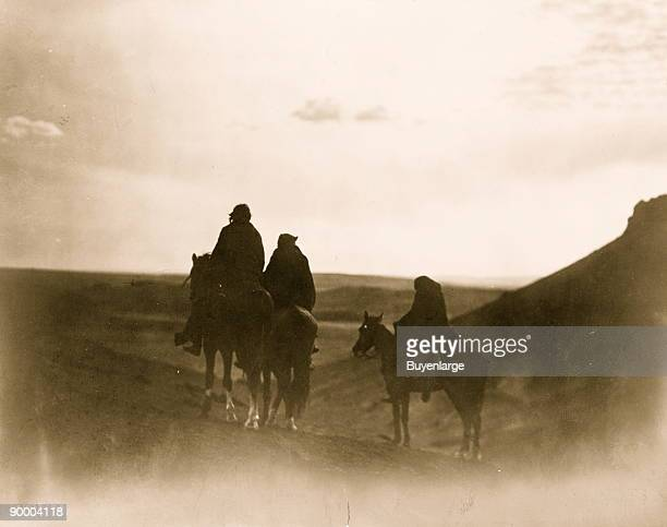 Three Navaho Indians on horseback, silhouetted on black buttes, in evening light.