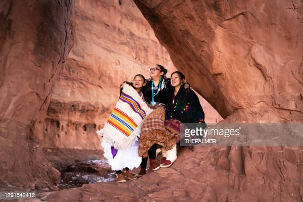 three navajo sisters sitting and talking on a rock formation in monument valley - arizona - navajo culture stock pictures, royalty-free photos & images