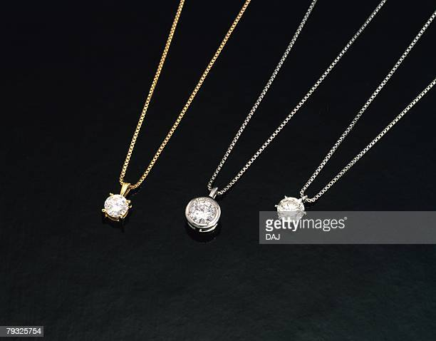 Three necklaces with diamonds, high angle view, black background