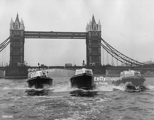 Three new fibre glass River Patrol vessels speeding down the River Thames Tower Bridge can be seen in the background