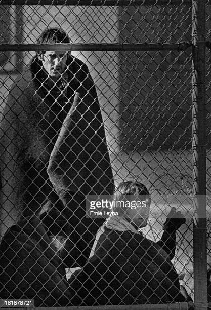 FEB 4 1980 FEB 5 1980 Three new Mexico State Penitentiary Inmates Huddle Along side the Fence Monday They were being kept in the prison yard...