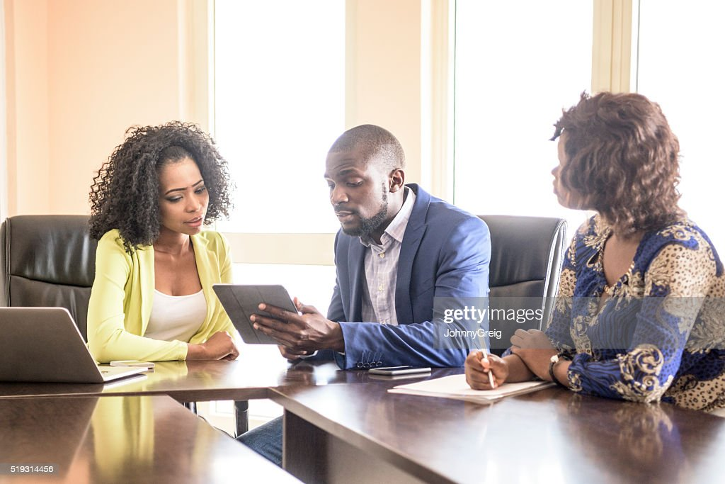 Three Nigerian colleagues in business meeting with tablet : Stock Photo