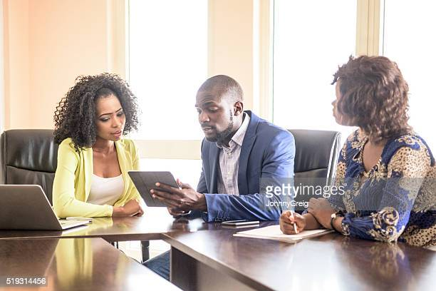 Three Nigerian colleagues in business meeting with tablet