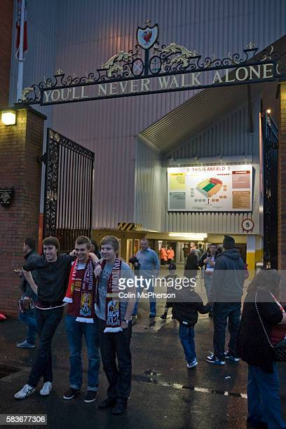 Three Northampton Town supporters posing for a photograph under the Shankly Gates at Anfield before their team's Carling Cup third round tie away to...