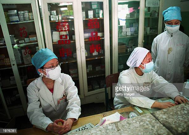 Three nurses, wearing protective masks as a precaution against Severe Acute Respiratory Syndrome , work in a hospital drugstore May 6, 2003 in...