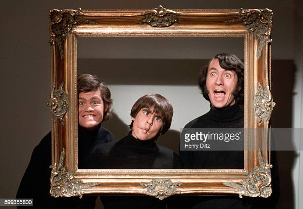 Three of The Monkees make faces behind an empty picture frame