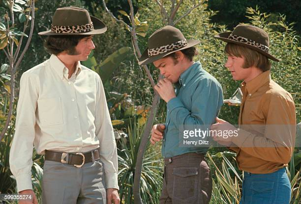 Three of The Monkees Wear brown hats on the outdoor set for their televison show