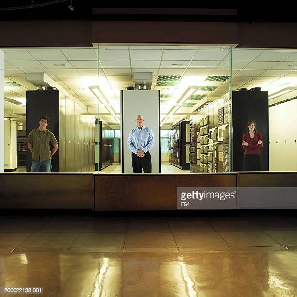 Three office workers looking out window in computer server room