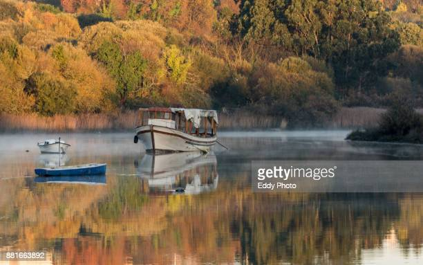 Three old boats in the river with autumm colors in the background at sunrise
