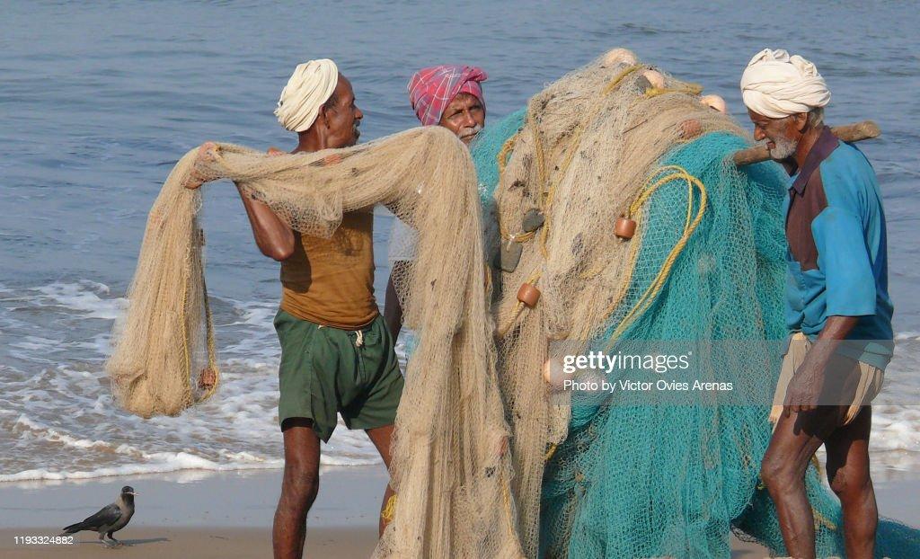 Three old local fishermen carrying their fishing nets on the beach in Gokarna, Karnataka, India : Foto de stock