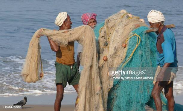 three old local fishermen carrying their fishing nets on the beach in gokarna, karnataka, india - victor ovies fotografías e imágenes de stock